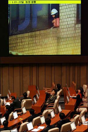 11일 국회 본회의 긴급현안질문에서 의원들이 용산 철거민 농성 장면을 보고 있다.
