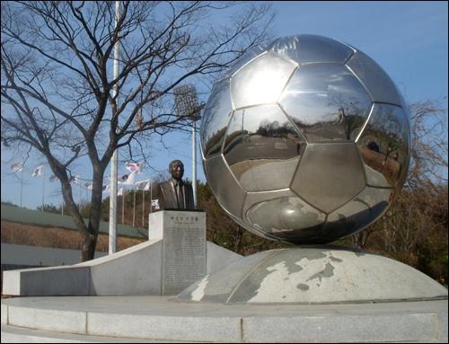 군산 종합경기장 입구에 세워진 채금석 선생을 상징하는 축구공과 흉상, 기념비