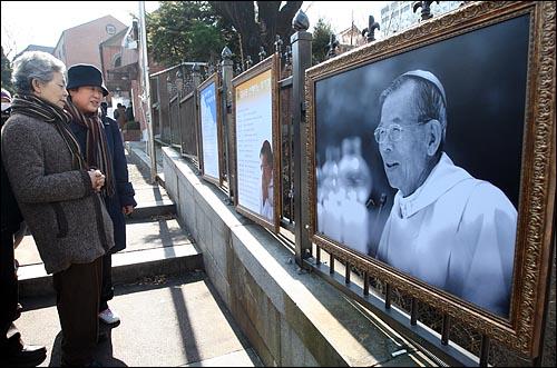 지난 16일 저녁 김수환 추기경이 선종한 가운데 17일 오전 서울 명동성당을 찾은 가톨릭 신자들이 전시된 김 추기경의 생전 사진을 둘러보고 있다.