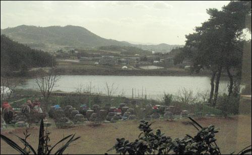 한씨 부부가 사는 황토너와집의 거실에서 대형유리창을 통해 바라본 바깥 풍경. 장독대와 저수지, 마을이 한눈에 보인다.