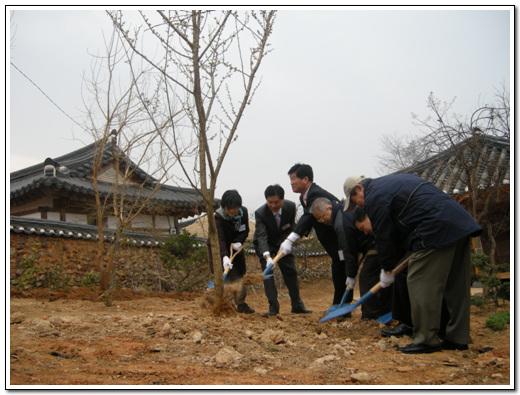 관계자들이 기념 식수를 하고 있다. 김홍남 이사. 김인회 대표 이사, 건축가 김원씨 등이  옛집 뒷뜰에 기념식수를 하고있다.