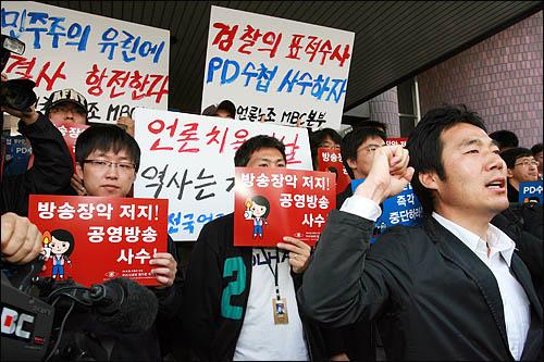 검찰이 'PD수첩'의 미국산 쇠고기 보도와 관련해 8일 오전 MBC본사 압수수색을 시도한 가운데, MBC 노조원들이 출입구를 봉쇄한 채 검찰 수사관들의 진입을 막고 있다.