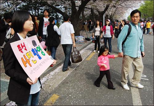 """""""아 민망해라"""" 12일 벚꽃 축제가 열리는 여의도 윤중로에서 사진 촬영 홍보판을 들고 있는 이지수 기자."""