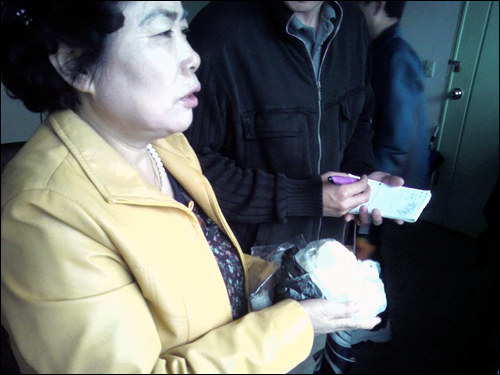 20일 무죄를 선고받은 미네르바 박대성씨의 어머니가 서울 구치소에서 두부를 들고 아들이 무죄 방면되기를 기다리고 있다(이 사진은 #5505 엄지뉴스로 1549님이 보내주셨습니다).