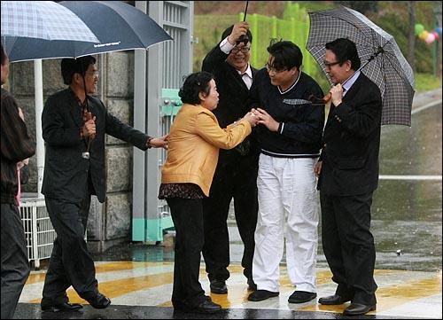 '미네르바' 박대성씨의 어머니 김춘화씨가 석방된 아들에게 두부를 먹으라며 건네고 있다.