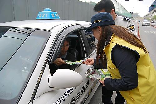 25일 KTX 천안아산역에서 택시운전기사에게 전단지를 배포하며 교통질서 지키기 캠페인을 벌이고 있는 마미폴 단원.