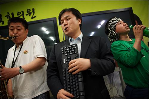 사진② 김종철 대변인이 '키보드 아코디언 연주실력을 뽐내고 있다. 그 옆에서 '진짜 색소폰'을 연주하는 손태현씨는 실력파 색소폰니스트다.
