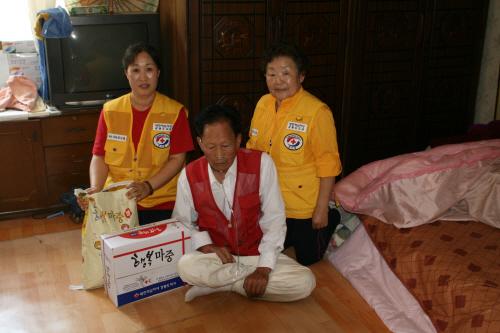 혼자 사는 홍승준어른을 찾아간 적십자회원 적십자 회원들이 쌀과 부식을 배달해주고 있다.
