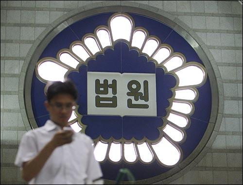 '촛불재판 개입' 의혹으로 엄중 경고를 받은 신영철 대법관의 거취를 놓고 일선 판사들이 반발하는 가운데 14일 오후 서울 서초동 서울중앙지방법원에서 법원 관계자가 법원 로고 앞을 지나고 있다.