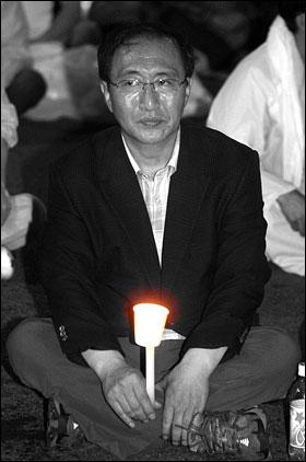 지난해 6월 29일 미국산 쇠고기 수입반대 촛불문화제가 열릴 예정인 서울시청 앞 광장을 경찰이 원천봉쇄하자 촛불을 든 진보신당 노회찬 대표가 수천 명의 시민과 함께 연좌시위를 벌이고 있다.