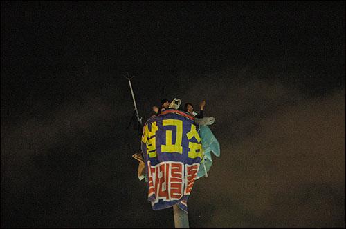 높이 30m의 고공철탑에서 69일째 농성을 벌이고 있는 로케트전기 해고노동자들. 지역에서 가장 큰 지지를 받고 있는 민주당은 이들의 외침을 철저히 외면하고 있다. 17일 밤 5.18전야제에 참석한 시민들이 위로의 손을 흔들자 함께 손을 흔들어 인사하는 두 노동자.