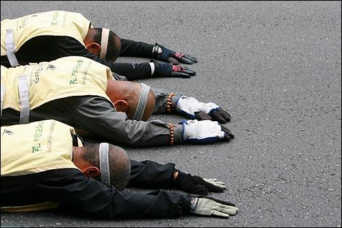 사람·생명·평화의 길을 찾아가는 '오체투지 순례단' 문규현 신부, 수경 스님, 전종훈 신부가 20일 오후 서울 남대문시장 부근 도로에서 오체투지를 하고 있다.