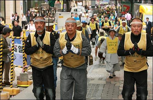 사람·생명·평화의 길을 찾아가는 '오체투지 순례단' 문규현 신부, 수경 스님, 전종훈 신부가 20일 오후 서울 명동성당을 향해 오체투지를 하고 있다.