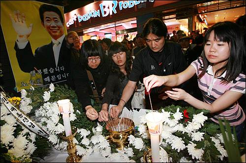 노무현 전 대통령 서거 소식을 접한 시민들이 23일 저녁 서울 덕수궁 대한문 앞에 마련된 간이 분향소를 찾아 분향하고 있다.