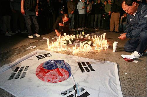 23일 밤 서울 덕수궁 대한문 앞에 마련된 노무현 전 대통령 임시 분향소를 찾은 시민들이 들고 있던 촛불을 세워 고인의 죽음을 애도하고 있다.