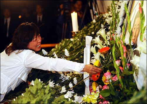 24일 새벽 노무현 전 대통령 빈소가 마련된 경남 김해 봉하마을회관을 찾은 한 조문객이 헌화하며 오열하고 있다.