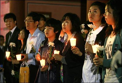 24일 밤 고 노무현 전 대통령 분향소가 마련된 서울 덕수궁앞에 국화꽃과 촛불을 든 시민들이조문 순서를 기다리고 있다.