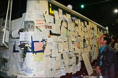 24일 밤 서울 덕수궁 대한문 앞에 마련된 노무현 전 대통령의 분향소를 켭켭이 둘러싼 경찰 차벽에 조문객들이 남긴 추모의 글이 빼곡히 붙어 있다.