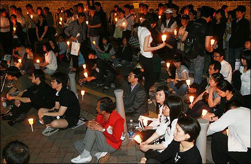 노무현 전 대통령을 추모하기 위해 25일 밤 서울 덕수궁 대한문 앞 분향소를 찾은 시민들이 촛불을 들고 노 전 대통령의 생전 모습을 담은 영상을 보고 있다.