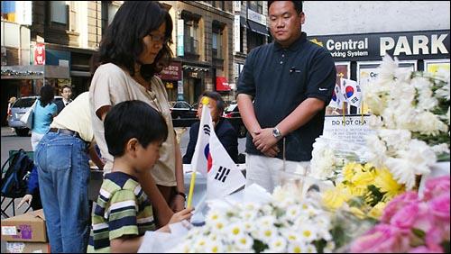 노무현 전 대통령을 추모하기 위해 맨해튼에 온 한 여성이 아들과 함께 묵념을 하고 있다.