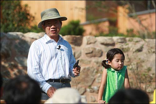 2008년 8월 13일. 생가마당에서 방문객들에게 인사말을 하고 있는 노무현 전 대통령. 손녀 서은양이 신기한 듯 관람객들을 보고 있다.
