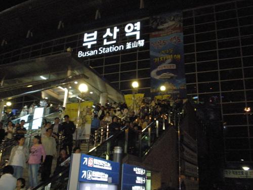 부산역 추모제에 많은 사람들이 참가해 무대가 보이지 않자 부산역사 계단에 앉아서 추모제를 보고 있는 시민들