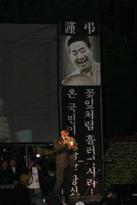 추모곡 부산시민이 故 노무현 전 대통령이 생전에 웃고 있는 모습이 담겨있는 현수막 앞에서 추모곡을 부르고 있다.