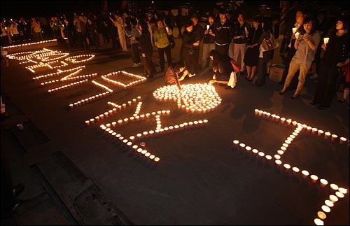 노무현 전 대통령의 유골함이 정토원에 도착할 예정인 가운데 29일 밤 경남 김해 봉하마을 노 전 대통령 사저 앞에서 추모객들이 촛불로 '노짱님 사랑해요' 글자를 만들고 있다.