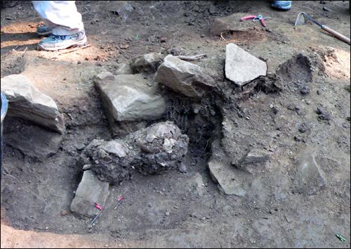 돌덩이에 짓눌려 있는 희생자 유해. 가운데 둥근 형태는 희생자의 두개골이다.