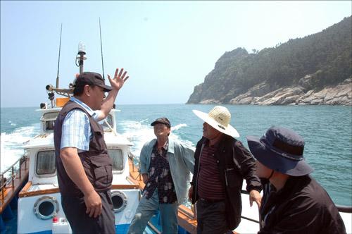 해상탐사 배를 타고 우제봉 암벽에 새겨졌다는 서불과차의 흔적을 찾으러 가고 있다. 갈곶마을 김옥덕 이장(좌)이 설명하고 있다.