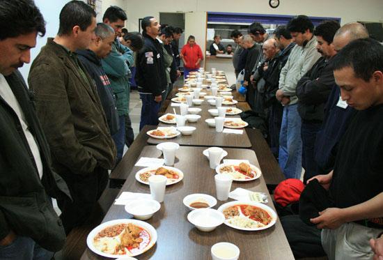 식사 기도를 하고 있는 노숙자들. 노숙자들의 식사는 지역사회에서 기부한 것이다.