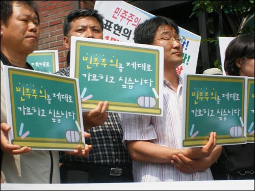 전교조 관계자들이 '민주주의를 제대로 가르치고 싶습니다'라는 피켓을 들고 있다.