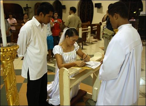 성당 신부 앞에서 혼인 서류에 서명하는 재혼 신부