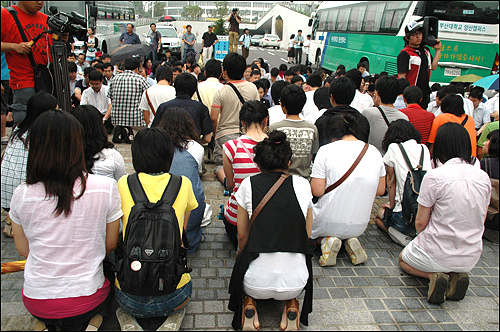 부산대 교직원들이 노무현 추모공연에 반대하며 정문에 앉아 있자 학생들이 무릎을 꿇고 20여분간 앉아 정문을 열어 줄 것을 호소하고 있다.