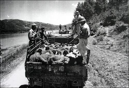 1950년 당시 암매장지로 끌려가고 있는 학살직전 사진. 오른쪽 뒷쪽 헌병과 공주형무소 특경대원(오른쪽 앞쪽), 경찰로 보이는(왼쪽 앞쪽) 사람들이 총을 들고 사람들을 감시하고 있다. 이 사진은 당시 영국 사진기자가 촬영한 것이다.