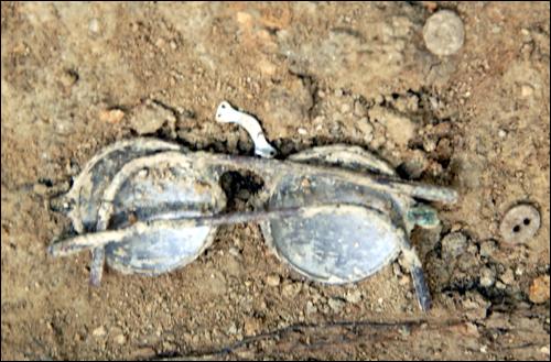 희생자의 것으로 추정되는 구덩이 속에서 발굴된 안경