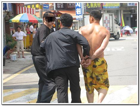 이주노동자(맨 오른쪽) 양손을 뒤로 하고 수갑을 채운 출입국직원(가운데)과 단속과정의 부당함을 항의하는 시민(맨 왼쪽)