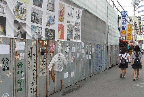 13일 오후 용산참사가 일어난 남일당 건물 맞은편 골목으로 고등학생들이 지나가고 있다. 철거용 임시벽에는 희생자들의 영정 사진 등 다양한 그림이 그려져있다.
