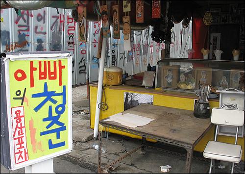 빈 가게에 차려진 '아빠의 청춘 용산포차'. 철거된 가게들의 그림과 주인들이 메뉴판에 그려져있다.
