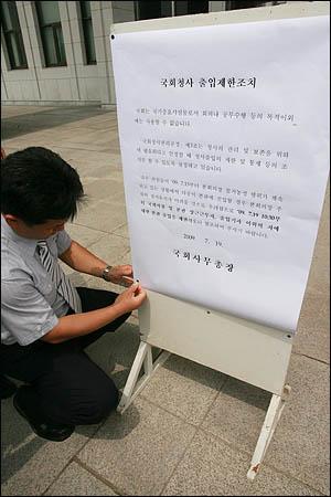 19일 오전 미디어법 처리를 둘러싸고 여야가 첨예하게 대치하고 있는 가운데 국회 관계자가 일반인들의 출입제한조치를 알리는 공고문을 국회 본청 정문에 붙이고 있다.