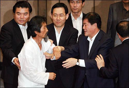 22일 미디어법 강행처리를 저지하기 위해 본회의장에 입장한 강기갑 민주노동당 의원이 의장석쪽으로 가려하자 한나라당 의원들이 에워싸 막고 있다.