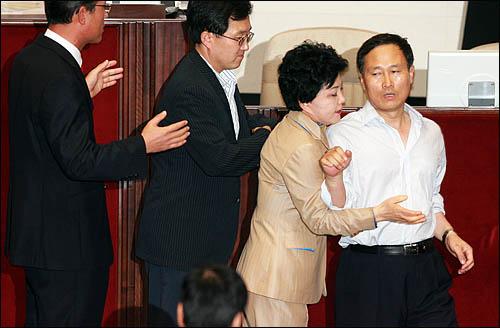 4.29 재보선에서 당선된 홍영표 민주당 의원이 22일 미디어법 강행처리를 저지하기 위해 본회의장에 입장, 의장석쪽으로 가려하자 한나라당 의원들이 에워싸 돌려세우고 있다.