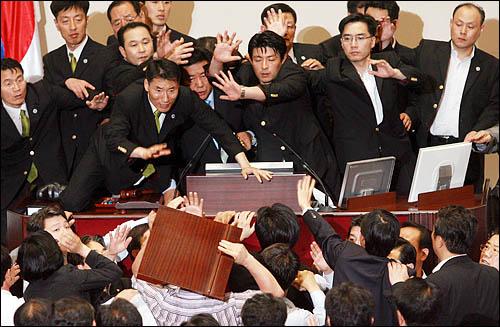 미디어법 강행처리를 저지하기 위해 22일 국회 본회의장에 입장한 강기정 민주당 의원이 이윤성 부의장 앞으로 다가가 거세게 항의하자 경위들이 이 부의장을 필사적으로 에워싸 보호하고 있다.