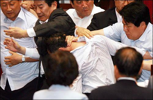 22일 국회 본회의장에서 미디어법 강행처리를 저지하려는 홍영표 민주당 의원을 한나라당 의원들이 힘으로 제압, 강제로 끌어내고 있다.