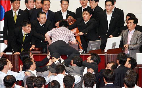 미디어법 강행처리를 저지하기 위해 22일 국회 본회의장에 입장한 강기정 민주당 의원이 이윤성 부의장이 앉아 있는 의장석쪽으로 뛰어올라 거세게 항의하고 있다.