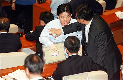 한나라당이 22일 끝내 미디어법 강행처리를 시도하자 국회 본회의장에 입장한 천정배 민주당 의원이 신지호 한나라당 의원 자리에 앉아 표결을 저지하고 있다.