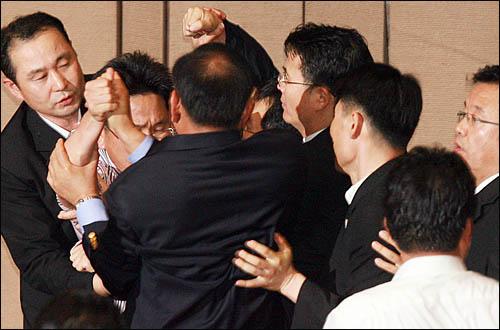 한나라당이 22일 끝내 미디어법 강행처리를 시도하자 국회 본회의장에 입장한 강기정 민주당 의원이 직권상정을 강행한 이윤성 국회부의장에게 항의, 김효재 한나라당 의원과 경위들에 둘러싸여 몸싸움을 벌이고 있다.