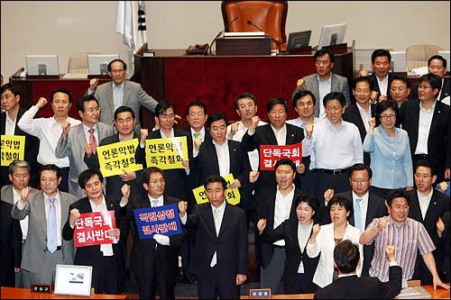 한나라당이 22일 전례없는 재표결에 대리투표 논란까지 일으키며 미디어법 강행처리를 시도한 국회 본회의장에서 민주당 등 야당의원들이 '원천무효'를 주장하며 '날치기 상정'을 규탄하는 구호를 외치고 있다.