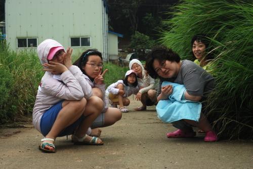 갯벌로 가는 길에서 고장난 트랙터 덕분에 갯벌로 걸어가던 아이들과 아낙네들이 길가에 모여 앉았다.