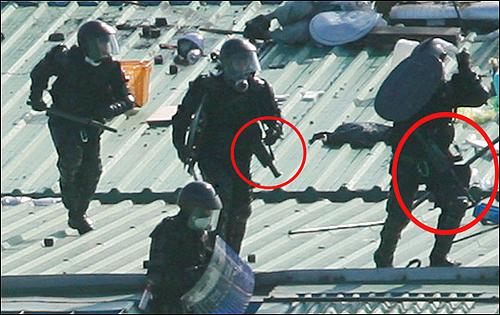 """정체를 두고 논란이 일었던 고무총탄에 대해 경찰이 """"폭동진압용으로 사용하고 있다""""고 시인했다. 붉은 원 안의 총기가 고무총.(사진제공: 노동과세계 이명익)"""